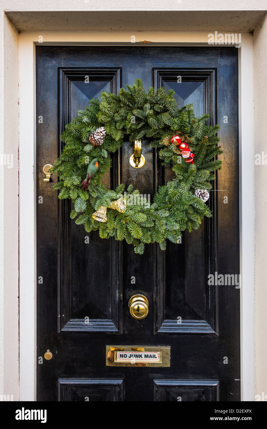 A traditional Christmas fir-tree wreath hanging on a black house door, Skerries, north County Dublin, Ireland - Stock Image