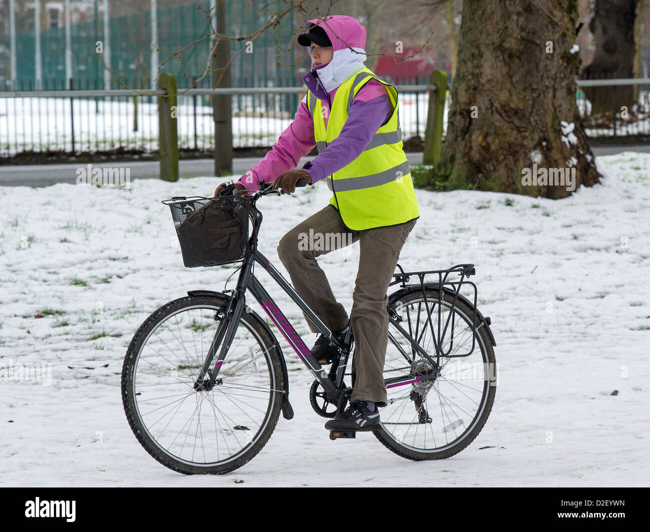 A cyclist is well wrapped up as they cross Clapham Common. The chilly weather continues to affect South London, - Stock Image
