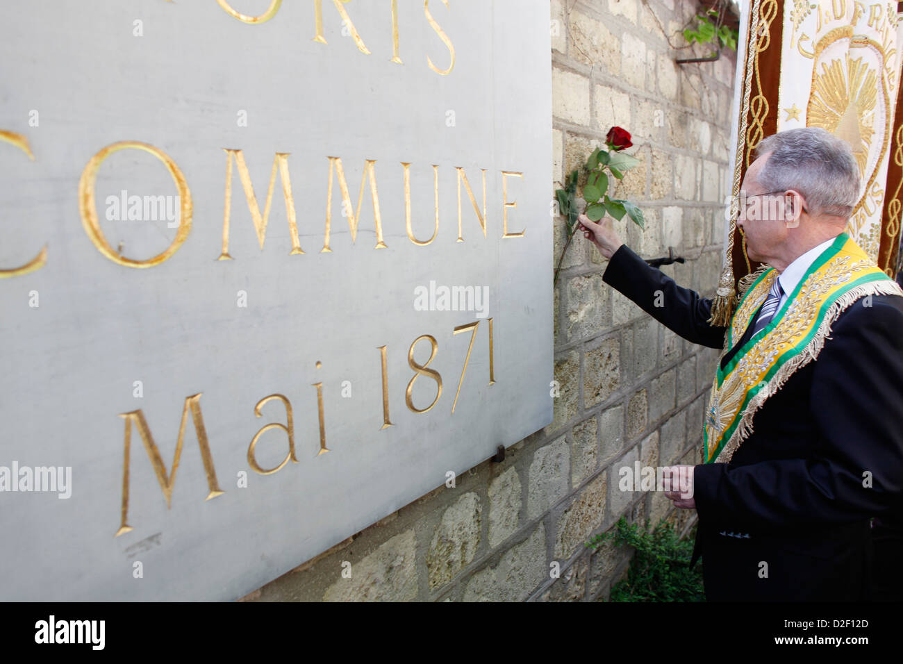 Freemason placing a rose on the Mur des Federes in the Pere Lachaise cemetery (commemorating the victims of the - Stock Image