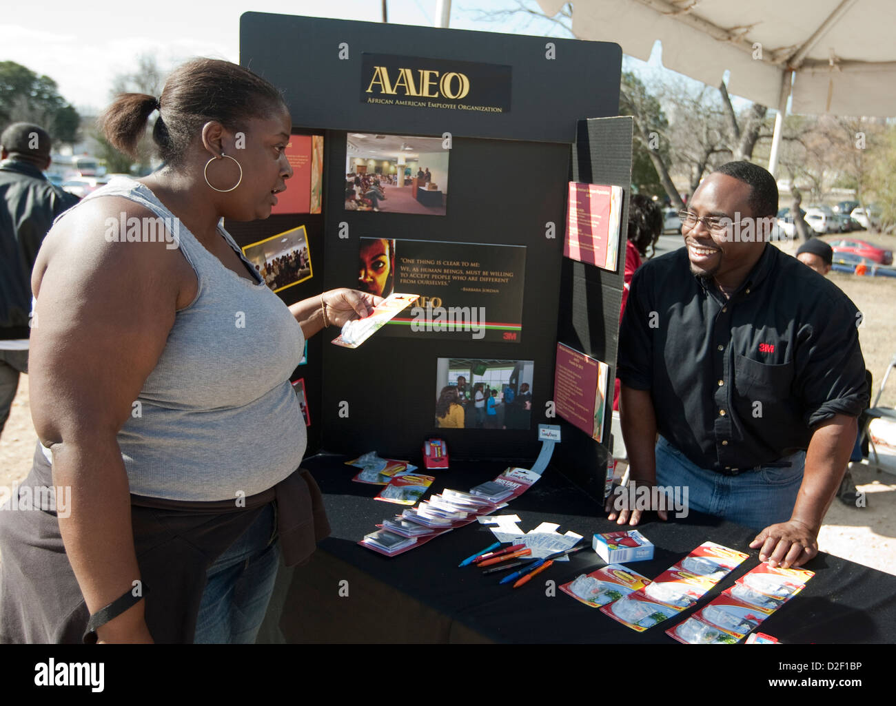 Male representative of the African-American employee organization, speaks to interested female festival attendee Stock Photo