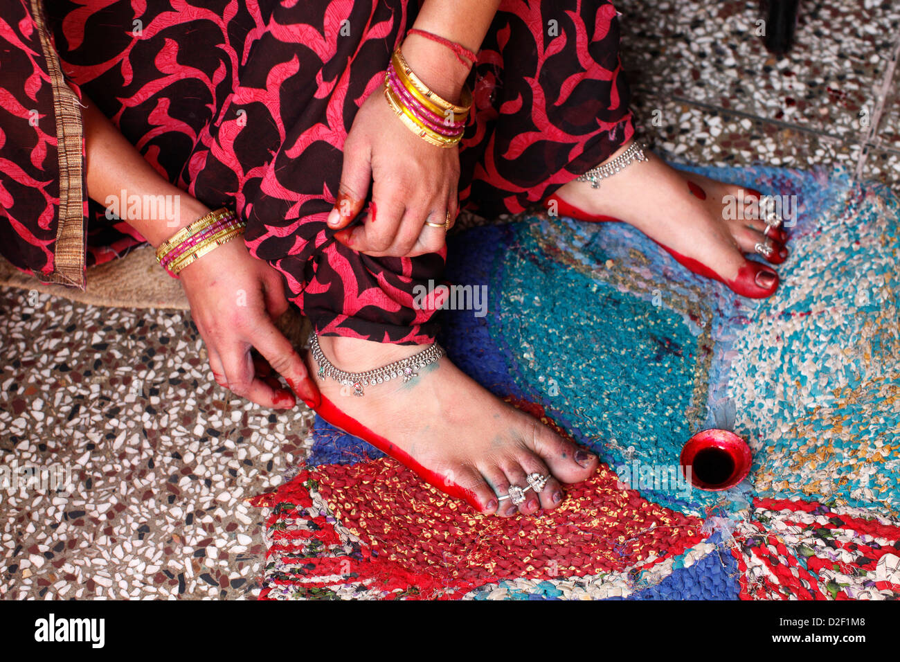 Woman applying red dye on her soles Goverdan. India. - Stock Image