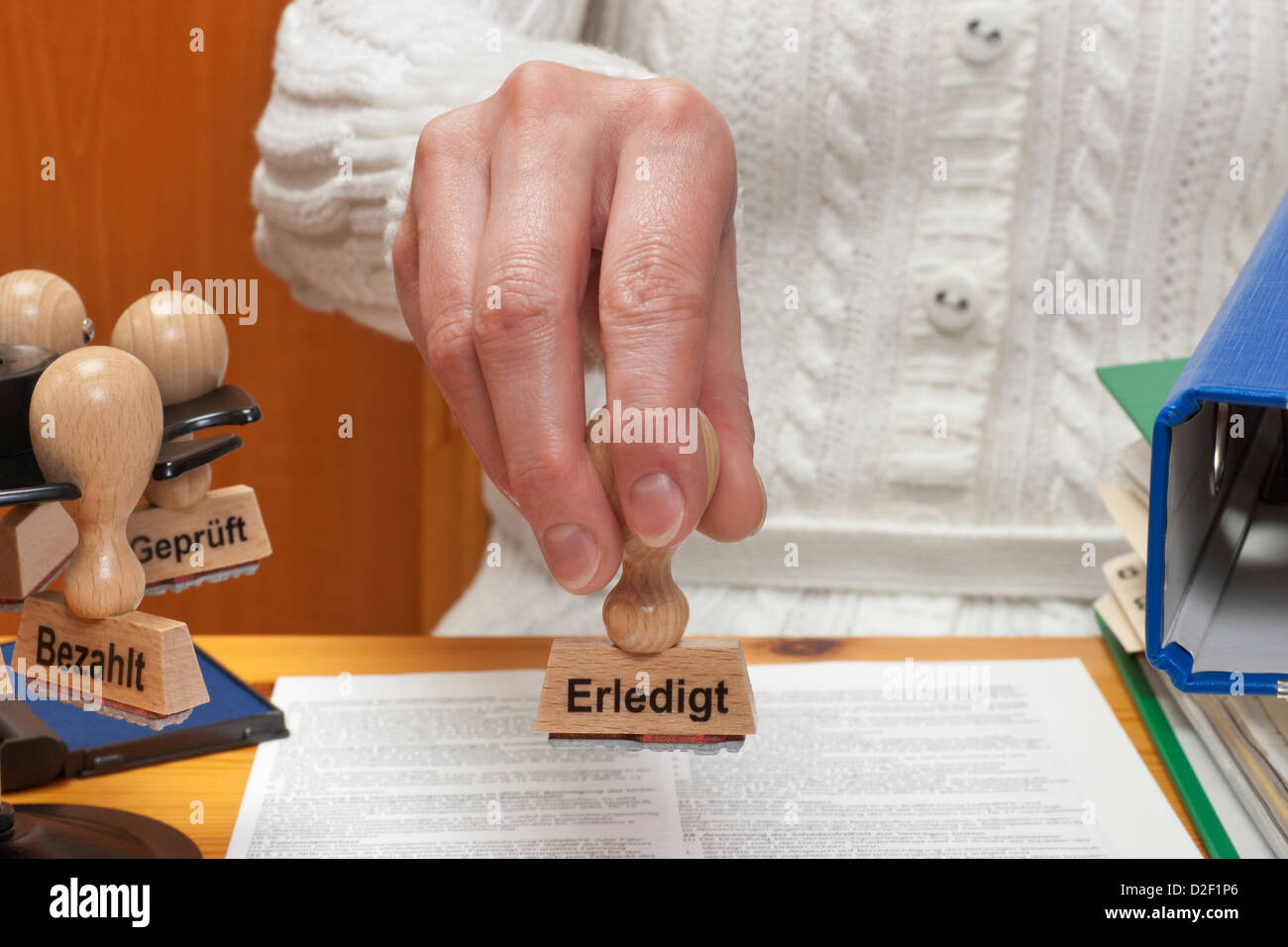 a stamp with the German inscription finished is held in the hand Stock Photo