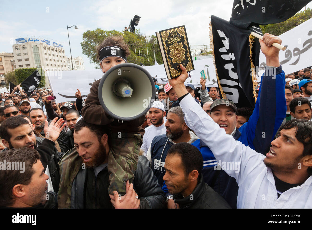 Radical islamists demonstrating in Tunis. A child is calling muslims to Jihad. The stripe he wears on his forefront - Stock Image
