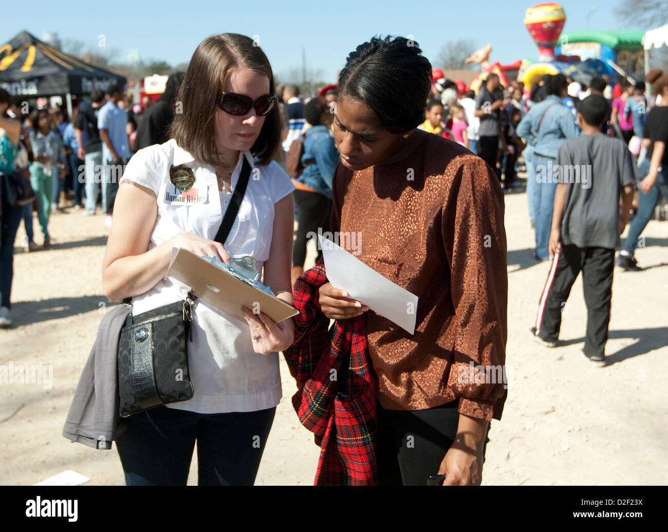 January 21st, 2013: White woman asks African-American to sign petition in favor of human rights at an MLK Jr. outdoor - Stock Image