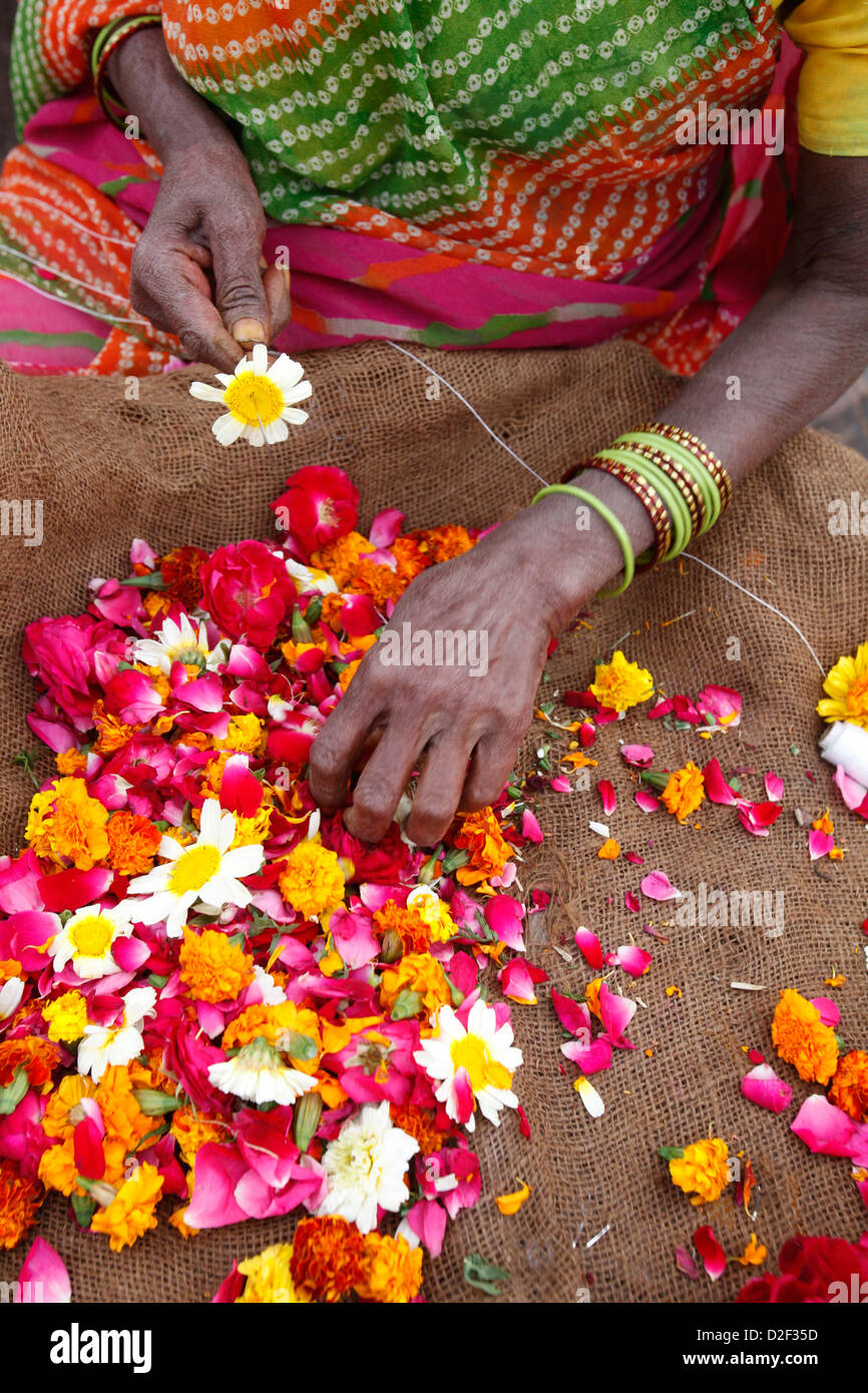 Woman making and selling garlands outside a Hindu temple Goverdan. India. - Stock Image