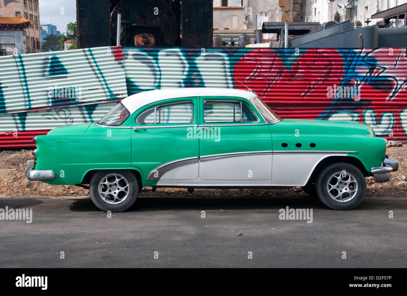 Classic American 1950's Car in front of Graffiti Wall on the Streets of Havana, Havana, Cuba - Stock Image