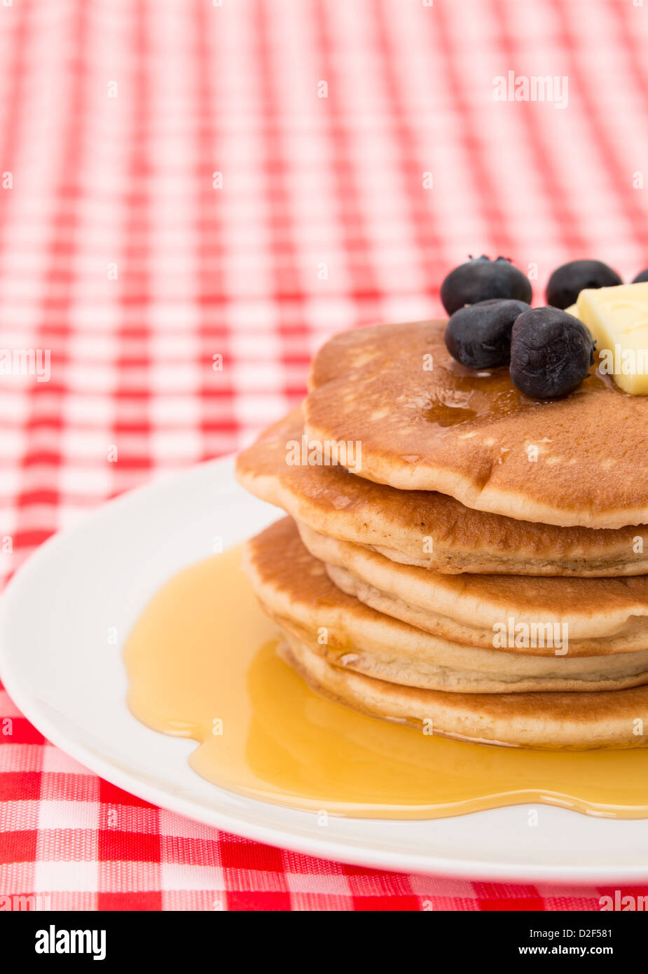 Fresh pancakes with blueberries, maple syrup and melting butter - Stock Image