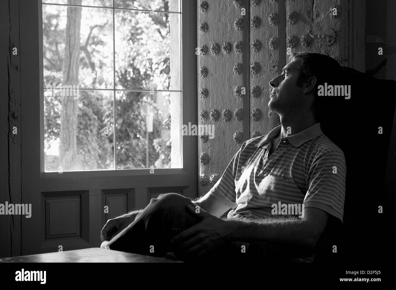 Mature man sitting, looking through the window. Black and white. - Stock Image