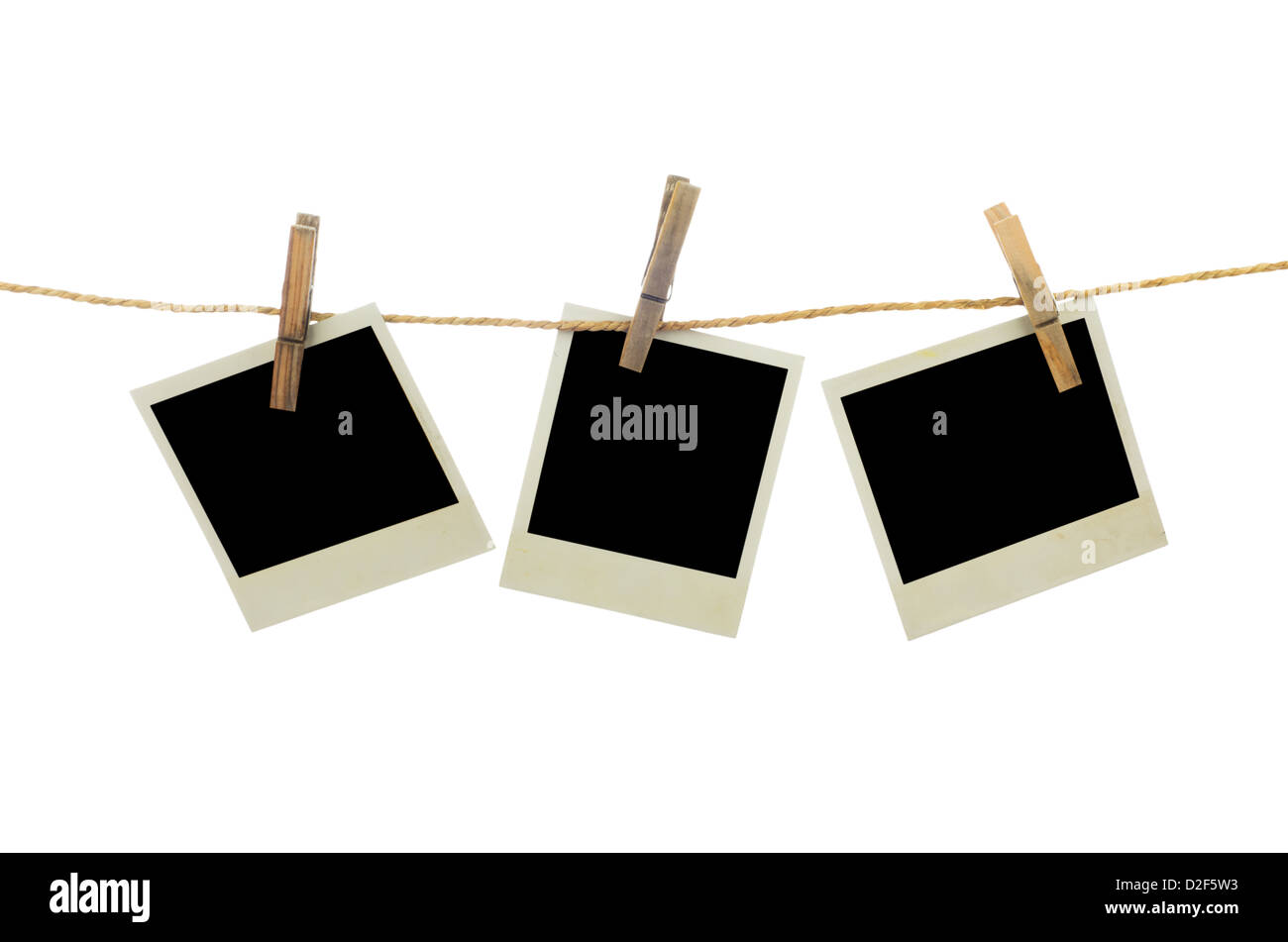 Three blank instant photos hanging on the clothesline. Isolated on white background. - Stock Image