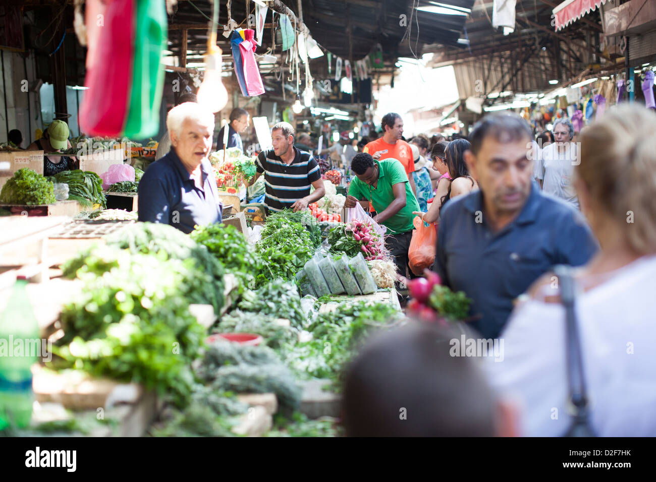 Market stall owners serve customers in the main market in Tel Aviv, Israel, on the day before Shabbat, the Jewish - Stock Image