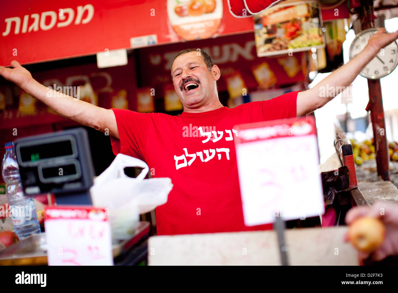 A market stall owner in Tel Aviv, Israel, sings to his customers as locals stock up ahead of Shabbat, the Jewish - Stock Image