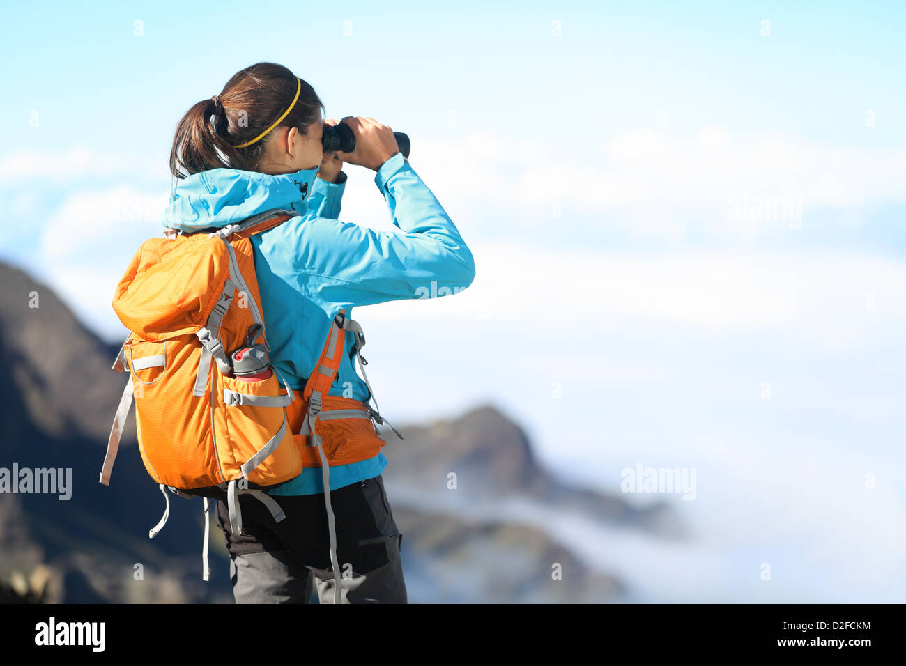 Mixed race young female hiker looking through binoculars enjoying spectacular view on mountain top above the clouds - Stock Image