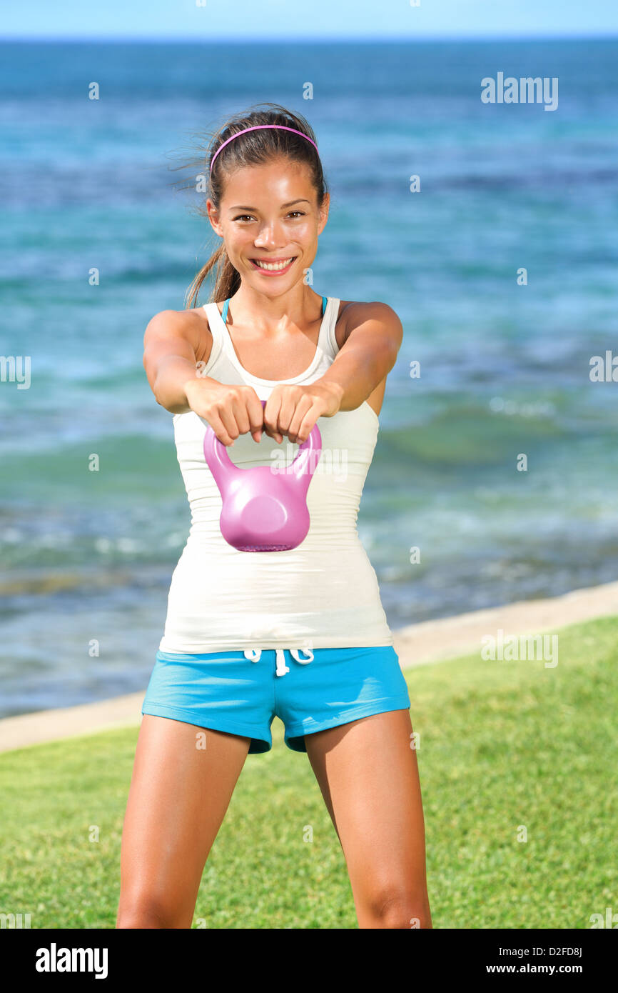 Portrait of beautiful young fit woman lifting kettlebell during strength training exercising outdoors on grass by - Stock Image