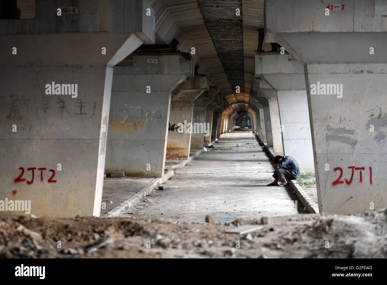 Shenzhen, China, a man sits hunched under a Strassenbruecke - Stock Image