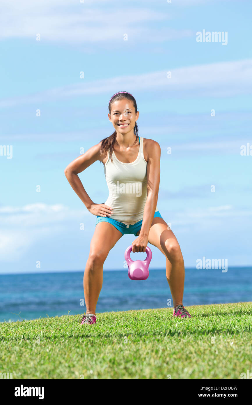 Beautiful young fit woman lifting kettlebell during strength training exercising outdoors on grass by the ocean - Stock Image