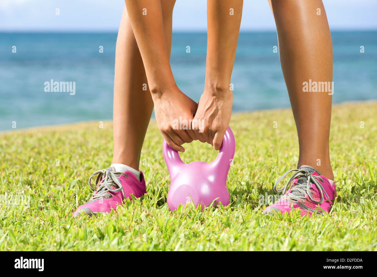 Low section of young fit woman lifting Kettlebell during crossfit exercise outside - Stock Image