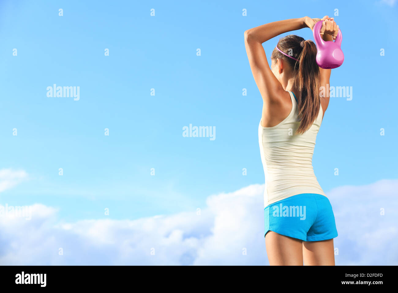 Back view of young fit woman using kettlebells outside during crossfit strength training against sky with copyspace - Stock Image