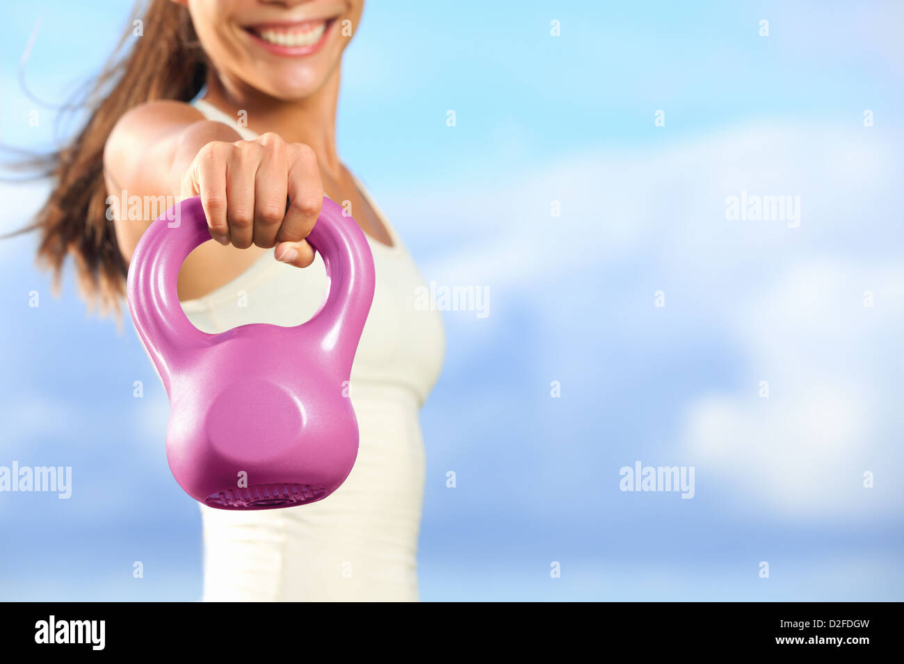 Closeup of woman's hand lifting kettlebell outside against blue sky with copy space - Stock Image