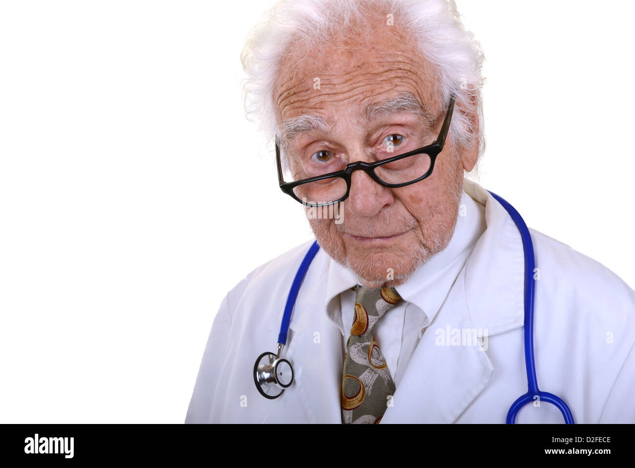 Kindly mature doctor wearing a white lab coat and glasses - Stock Image