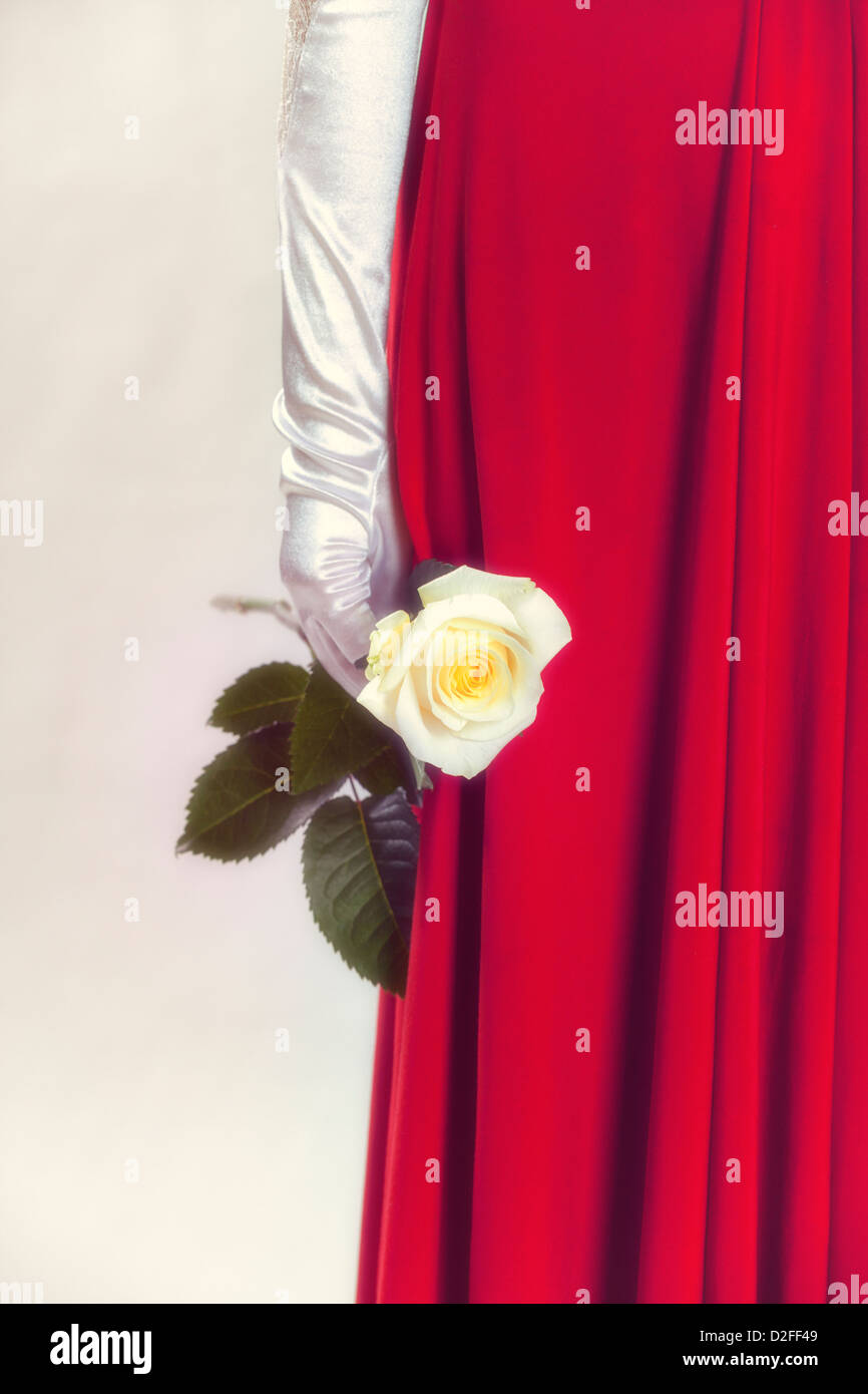 a woman in a red dress is holding a white rose in her hand - Stock Image