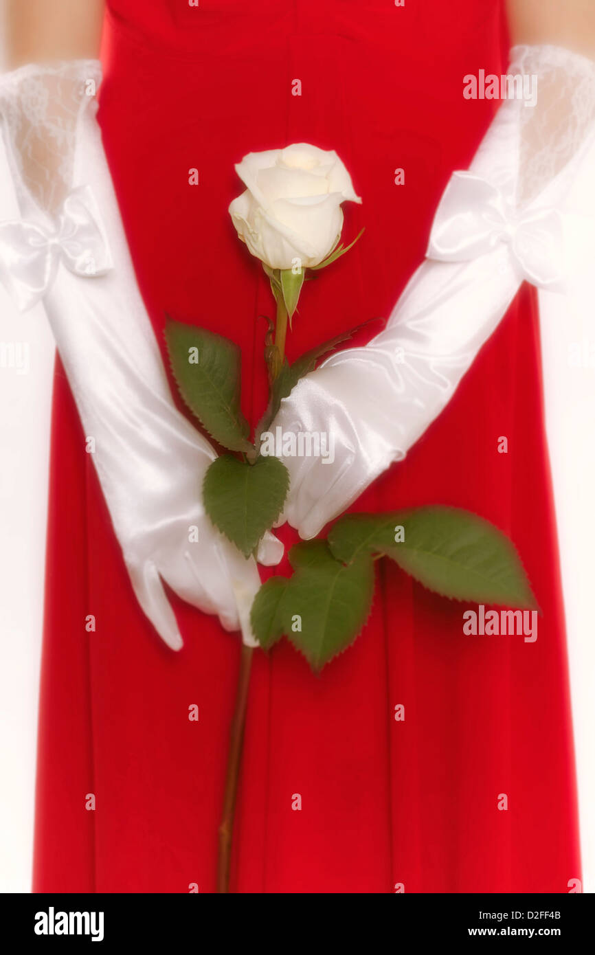 a woman in a red dress is holding a white rose in her hands - Stock Image