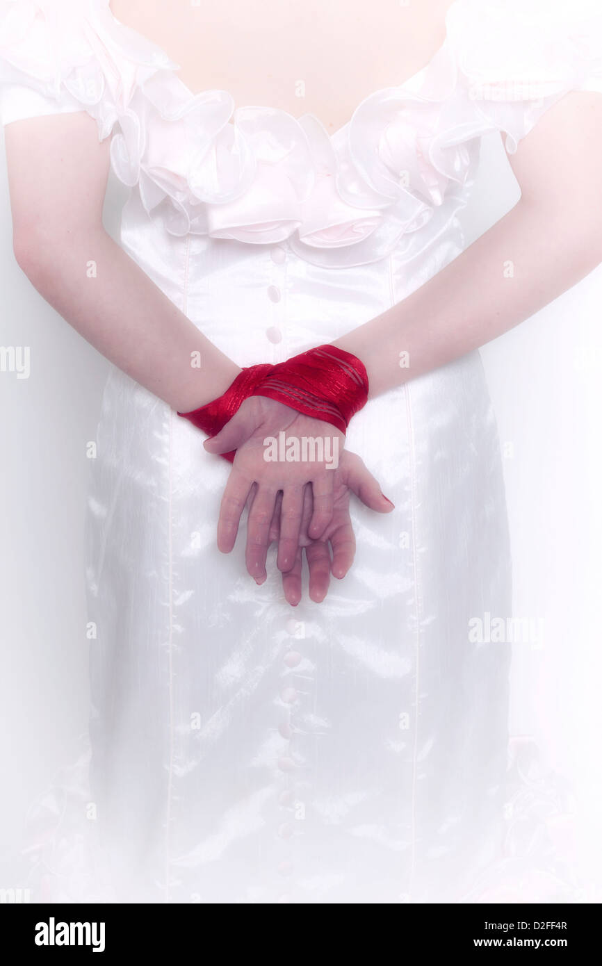 a woman in a white dress with tied hands - Stock Image