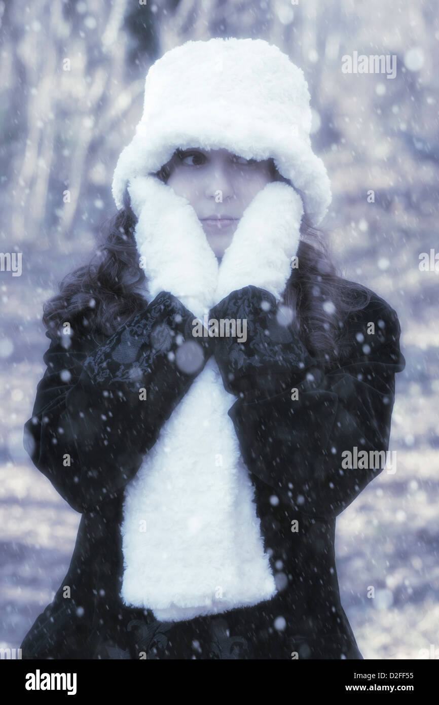 4d29e693d79ad0 a woman with a black coat, white gloves, scarf and hat outside during  snowfall