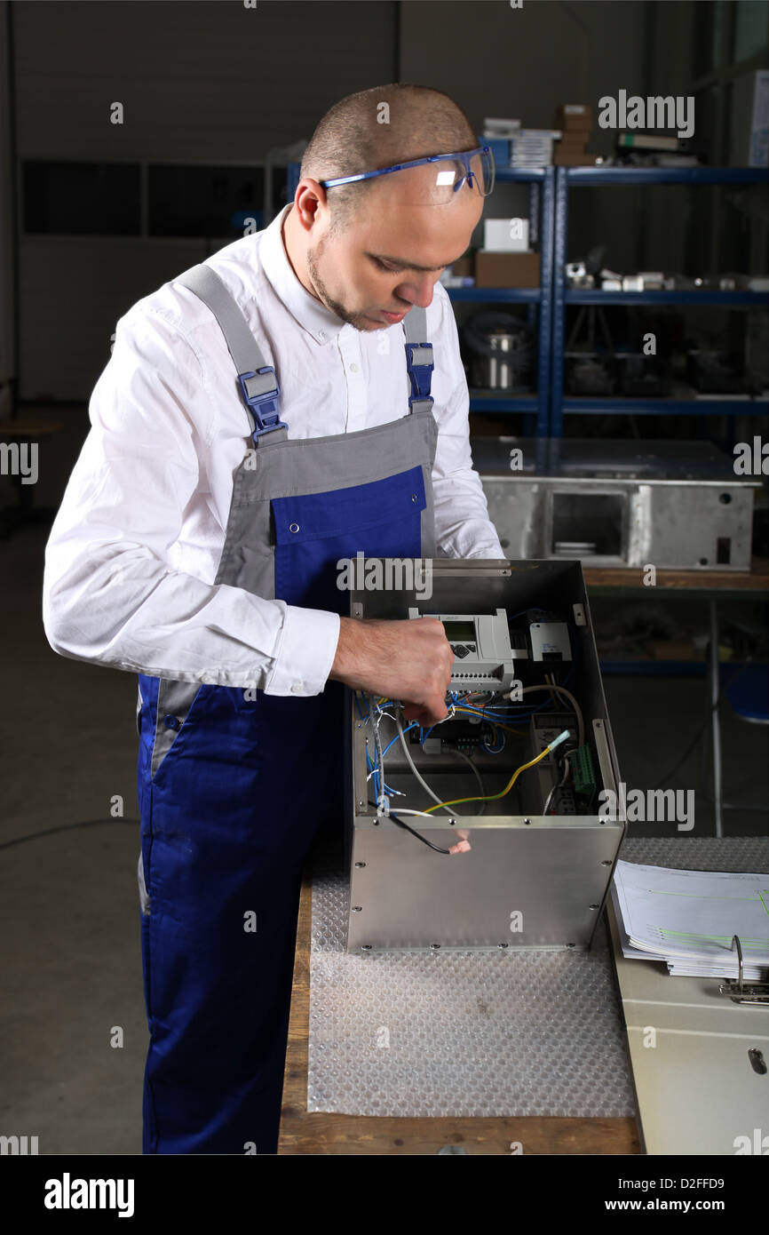 workman in blue overalls - Stock Image