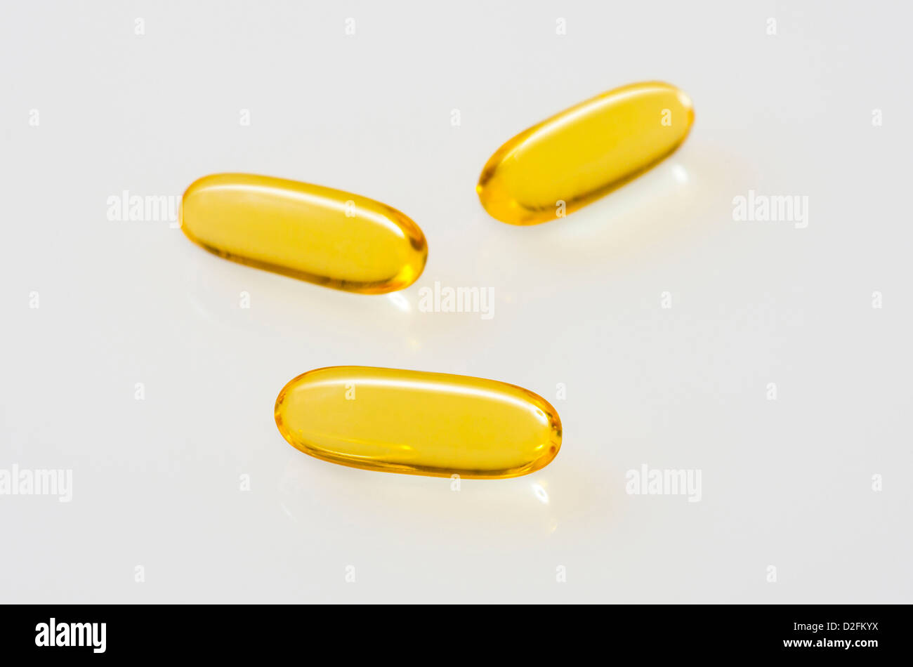Fish Oil Capsules on an off-white reflective background - Stock Image