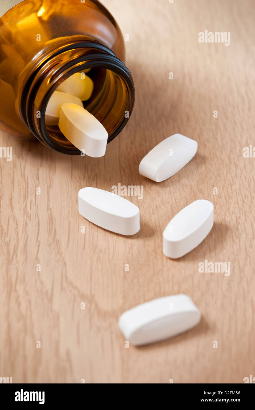 Pills bottle with some spilling out onto the table - Stock Image