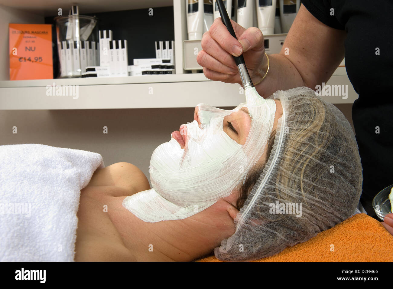 A woman is lying in a beauty salon and getting a facial mask on her face with a brush - Stock Image