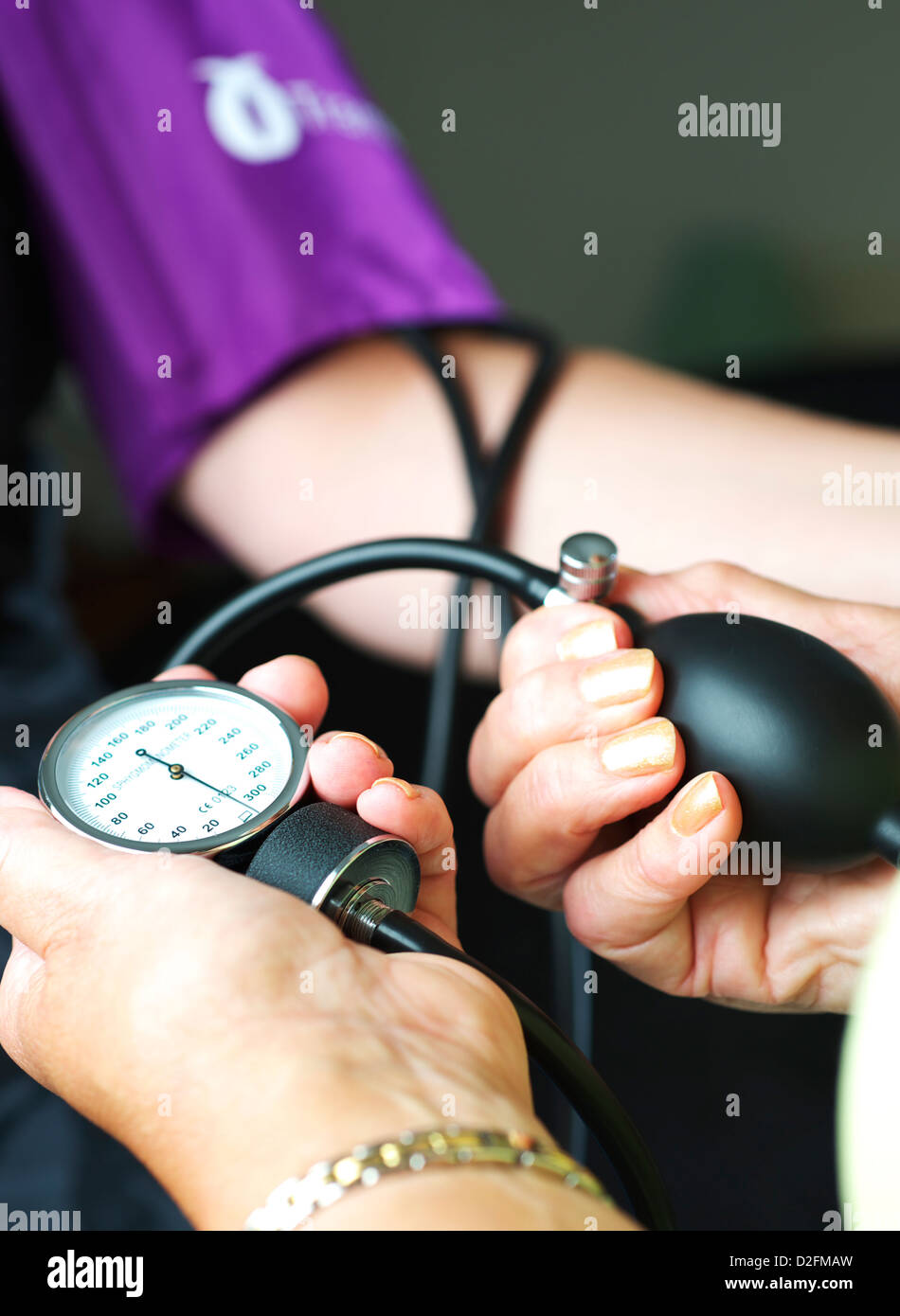Female blood pressure being taken in UK GP Health Centre by female doctor - Stock Image
