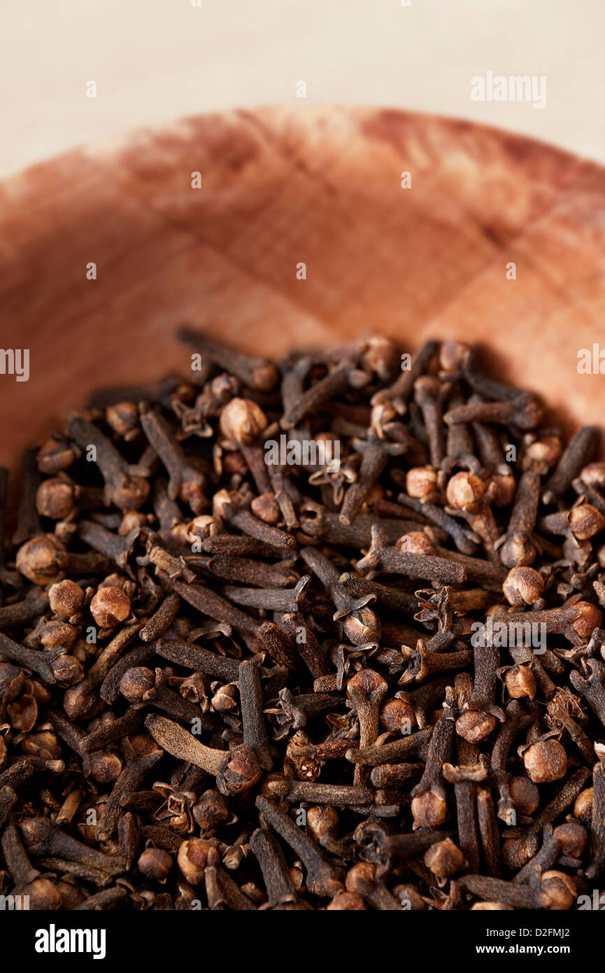 Cloves in a wooden bowl - Stock Image
