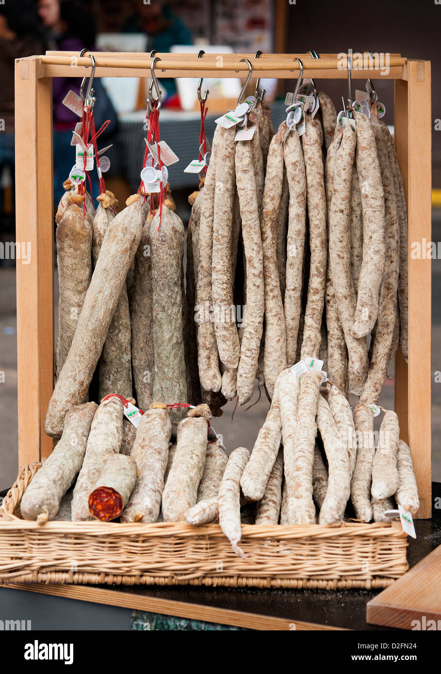 Selection of salami sausage hanging up in a market stall - Stock Image