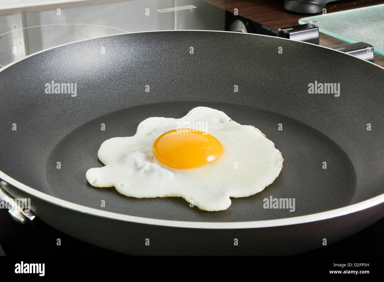 Egg frying in a frying pan on a ceramic hob - Stock Image