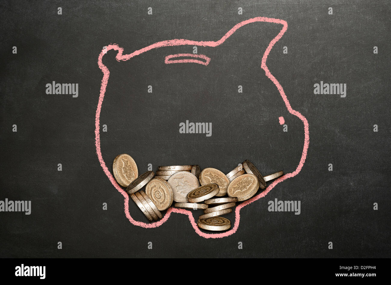Money (sterling) coins in a piggy bank drawn on a blackboard - Stock Image