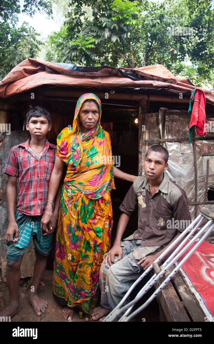 Sjojun, 14 years old with his brother and mother outside their house in the Tejgaon slum. Sjojun had polio and cannot - Stock Image