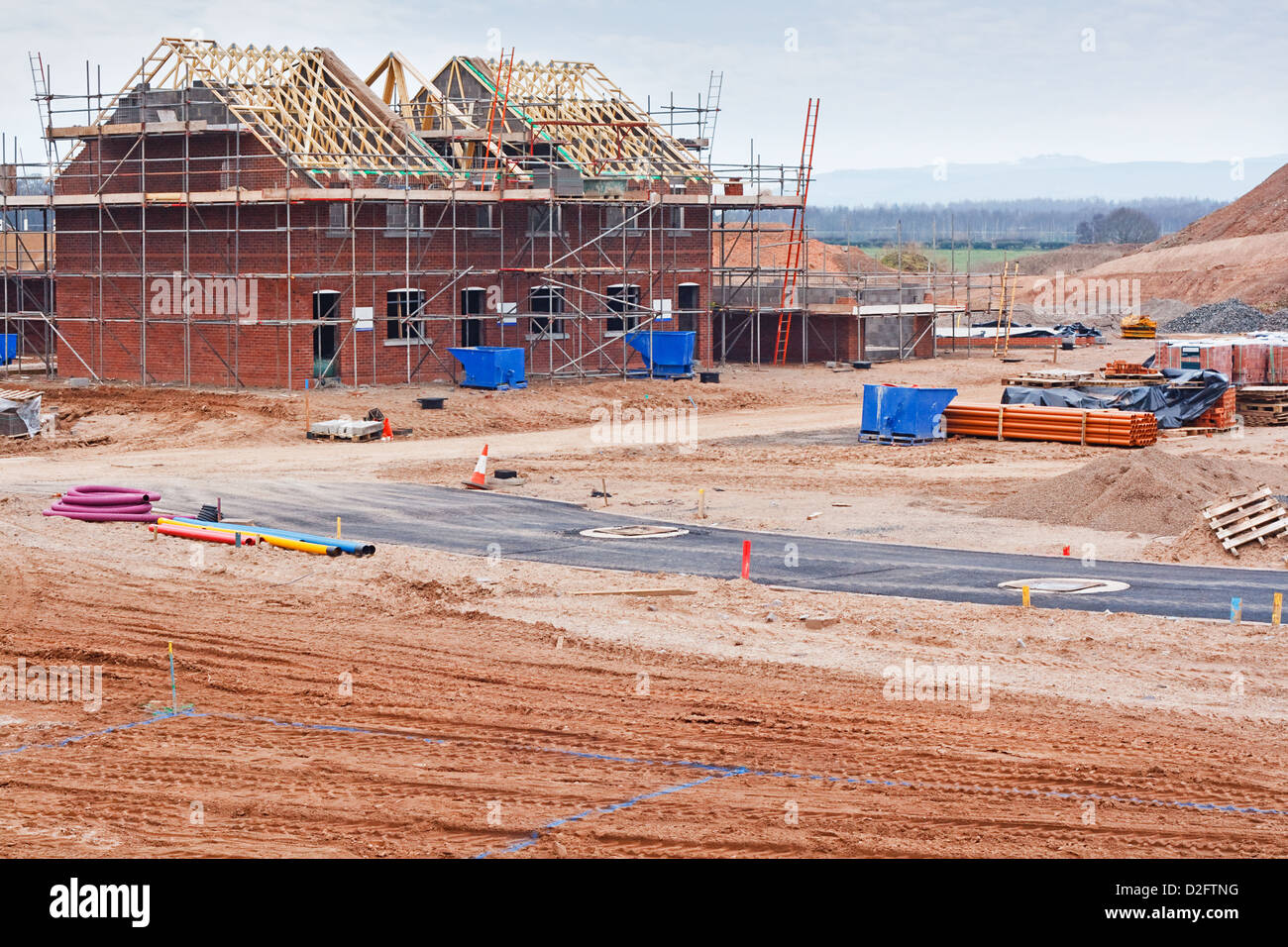 Partially built residential housing building site with homes in early stages of construction - Stock Image