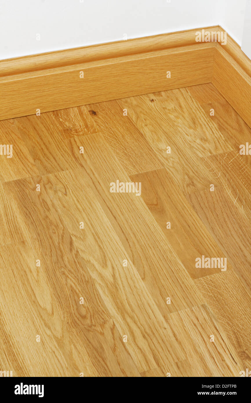 Close up showing some wood effect vinyl flooring and mdf imitation pine skirting boards in new build house - Stock Image