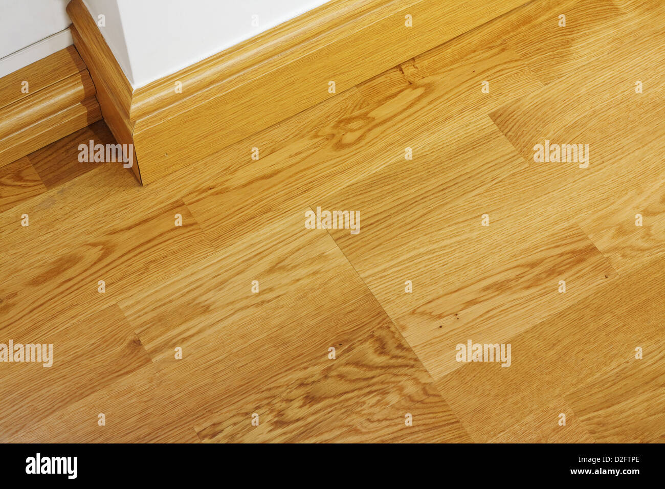Close Up Showing Some Laminate Flooring And Mdf Imitation Wood Skirting Boards In Newly Constructed House
