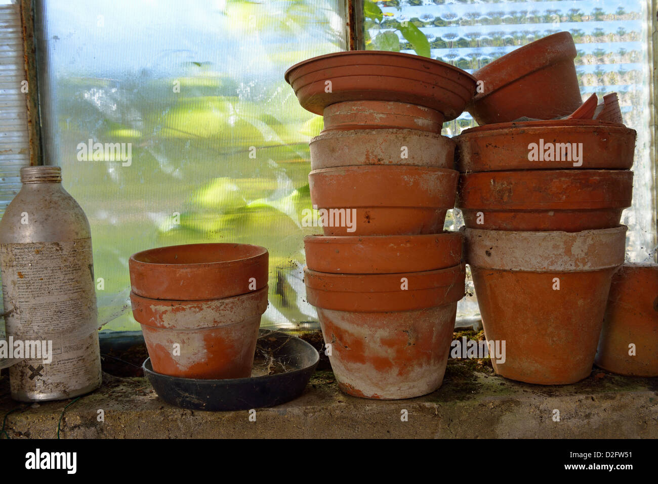 Stacked empty old plant pots by window in a garden shed - Stock Image
