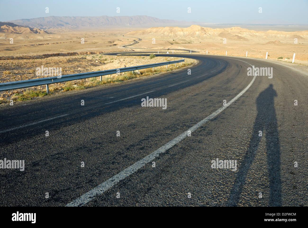 Man's shadow on a empty winding desert road, Tunisia Stock Photo
