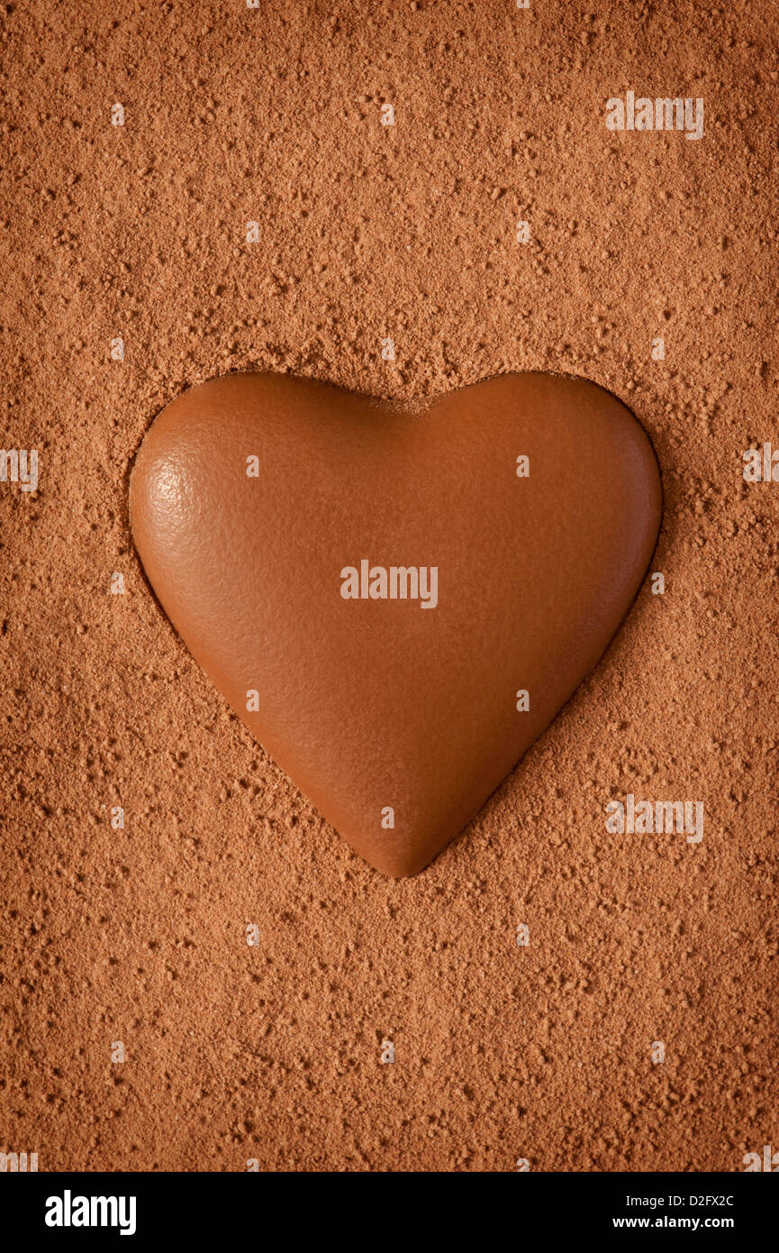 Milk chocolate heart on a textured background made from coco powder - Stock Image