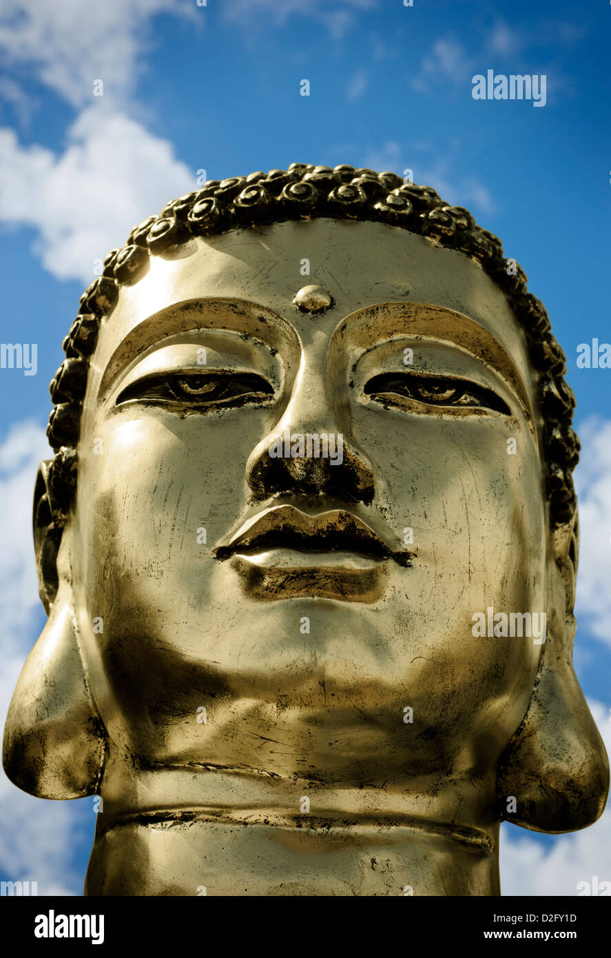 Close up detail of a gold Buddha Head against a cloudy blue sky - Stock Image