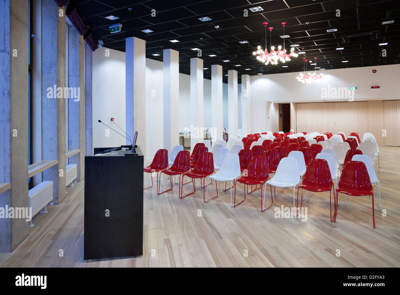 Modern large conference hall with lectern podium. Colorful chairs in university auditorium. Tartu Health Care College - Stock Image