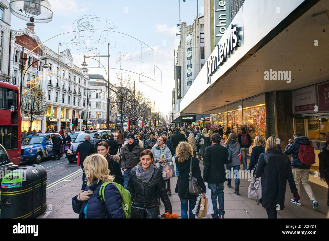 Shopping on a busy London street, Oxford Street, London at Christmas, UK - Stock Image