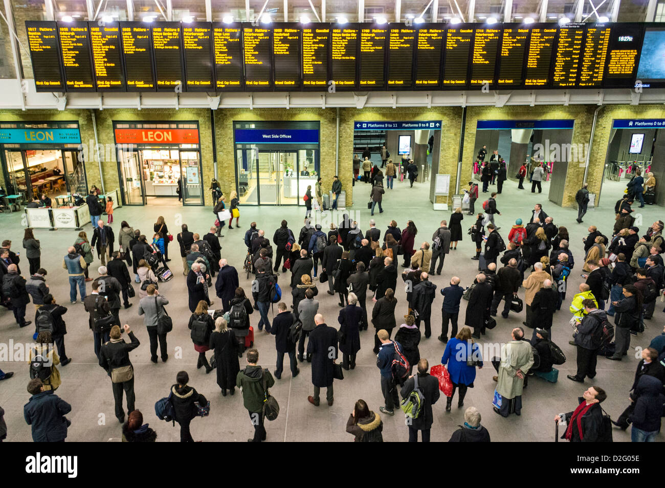 People at Kings Cross station, London, UK - looking at the departures boards at evening rush hour with cancelled - Stock Image