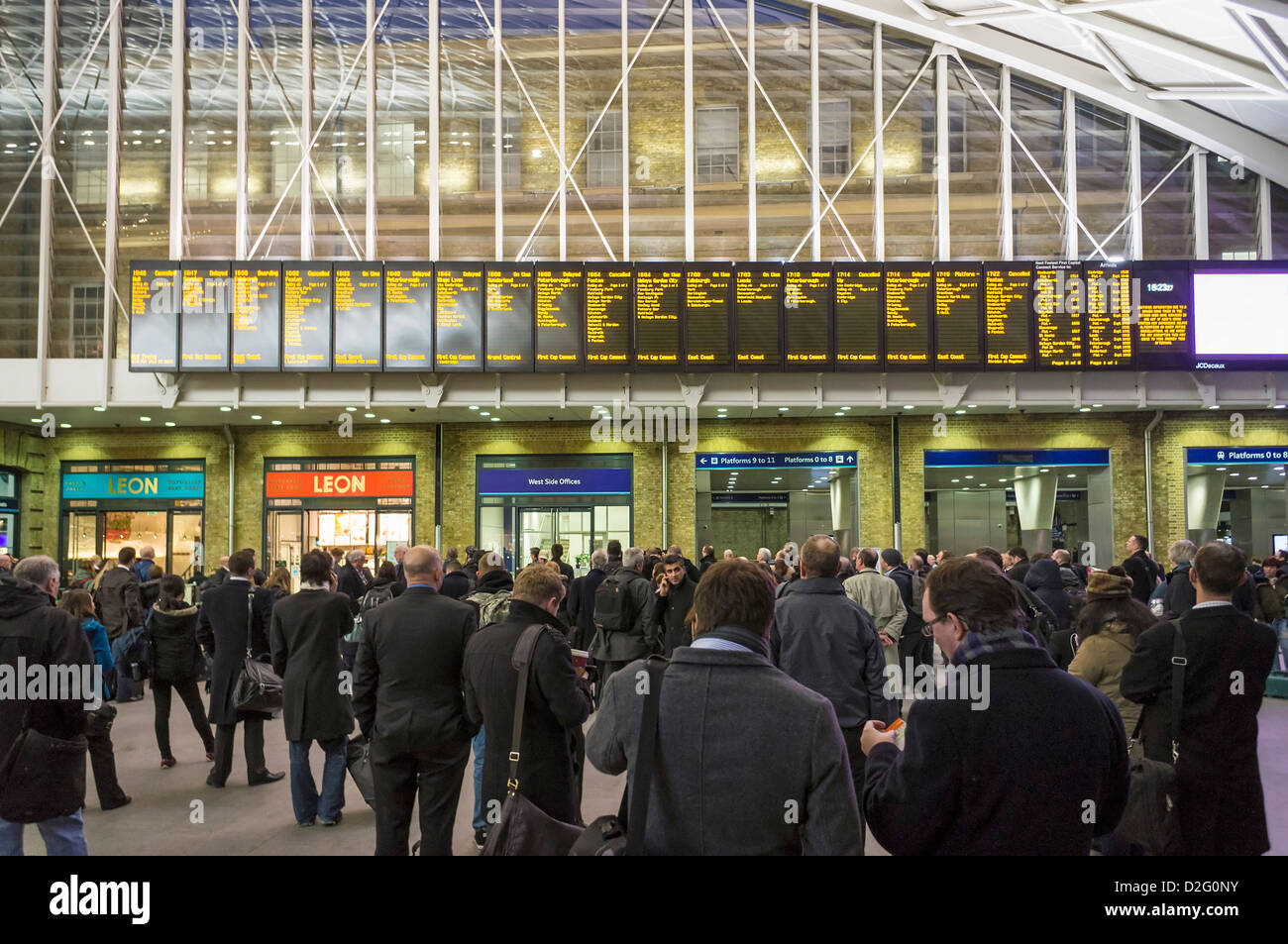 Commuters people looking at departure boards full of train delays cancellations at Kings Cross station, London, - Stock Image