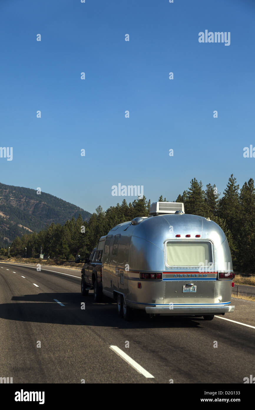 A classic silver Airstream travel trailer on I-90 in Montan USA - Stock Image