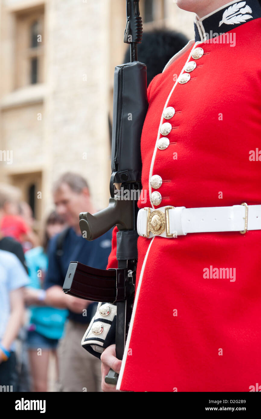 Close up detail of Royal Scots guard's tradition red uniform and rifle. Tower of London UK - Stock Image